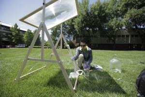 SEMPLICE, ECONOMICO, EFFICACE. I prototipi sono studiati per essere utilizzati nei paesi in via di sviluppo. Nell'immagine, Paul Shen al lavoro con una lente fresnel montata su un supporto in legno e con un contenitore in materiale trasparente permeabile ai raggi UV. Uno dei prossimi passi della sperimentazione consosterà nell'uso di batteri patogeni.(FOTO Prof. Ernest R. Blatchley III)