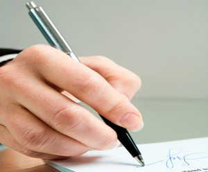 Photo of ballpoint in the female hand over a contract