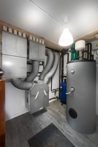 LOCALE TECNICO. In primo piano l'accumulo termico per l'acqua calda sanitaria e l'impianto di ventilazione forzata, supportato da una una batteria di post riscaldamento/raffrescamento nel condotto di mandata.